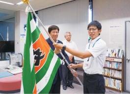 西村組合長に交通安全旗を手渡す高納共済担当