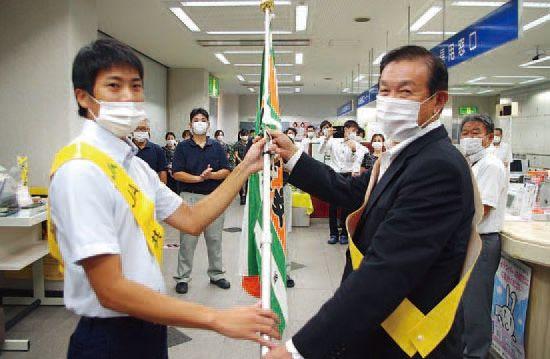 西村組合長に交通安全旗を手渡す高納共済担